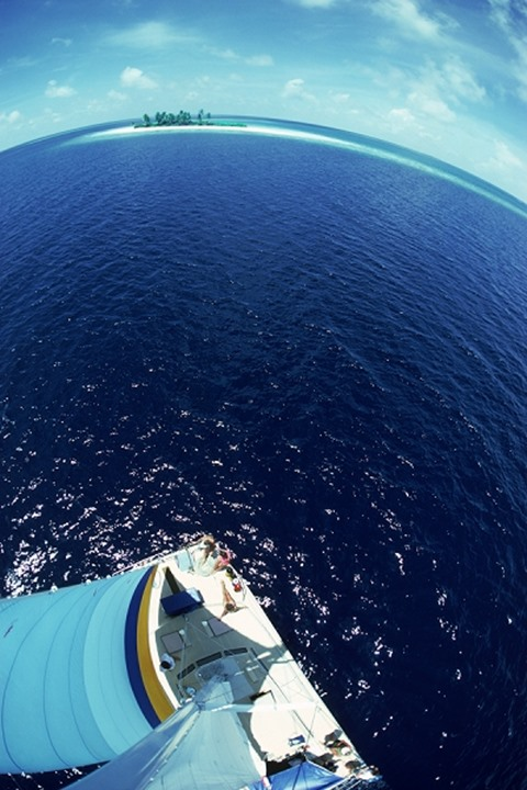 Elevated view of deserted Maldivian island from sailboat mast