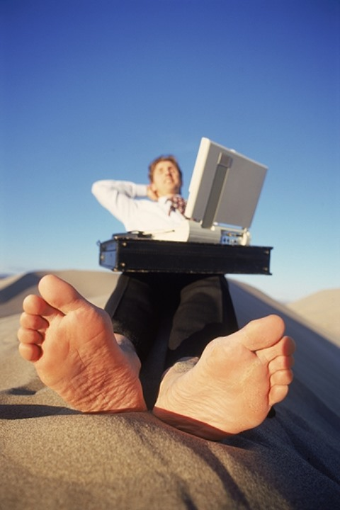 Barefoot businessman using desert sand for outdoor office space