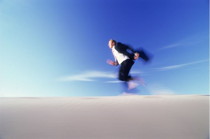 Businessman running across sand dune with briefcase