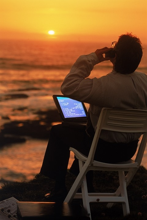 Man with laptop computer and cellphone on California coast at sunset