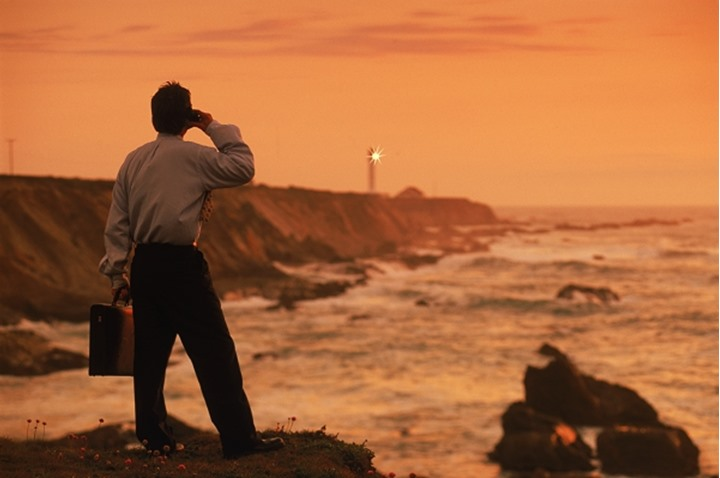 Businessman talking on cellphone near Point Arena Lighthouse on California coast