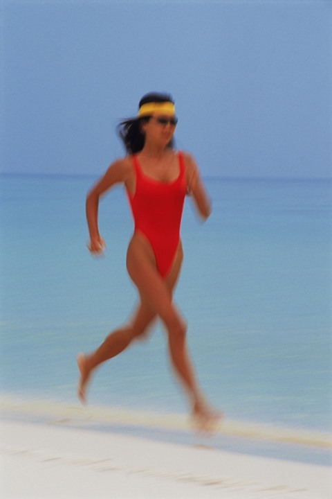 Woman in red swimsuit running along shore