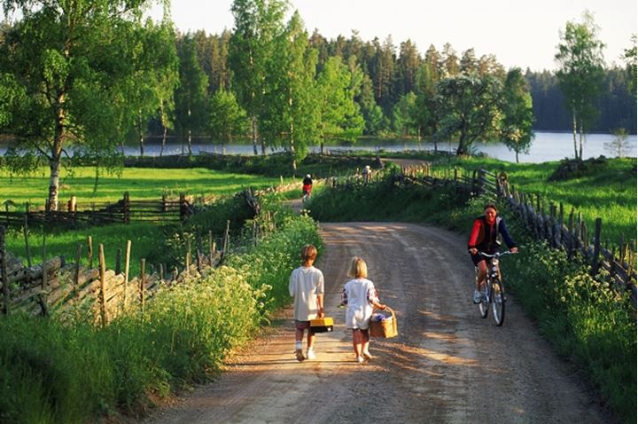 Children walking on country road with bicycler in Sweden