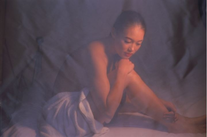 Woman of ethnic mix sitting on bed in soft light