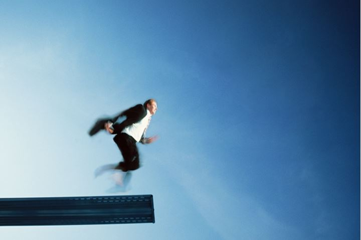 Businessman about to run off diving board