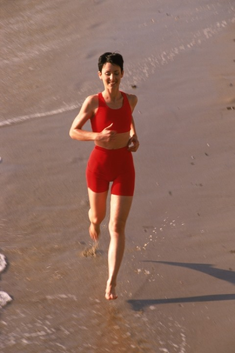 Woman in red running along sandy shore