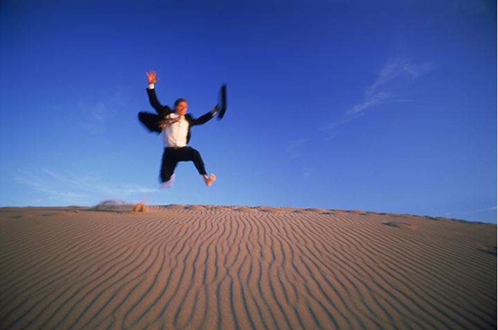 Businessman with briefcase jumping down sand dune
