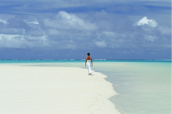 Lady in white dress on white sandbar under white clouds in Cook islands