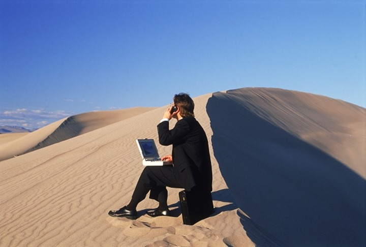 Businessman in desert with laptop computer talking on cellphone in his outdoor office
