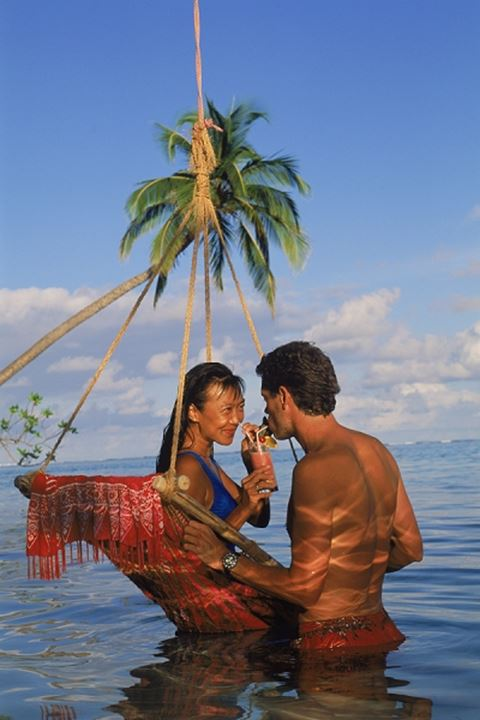 Couple sharing tropical drink in swing hanging from palm tree at sunset