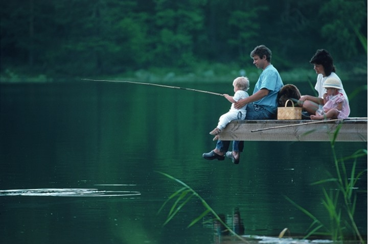 Family of four with their dog on fishing picnic in Sweden