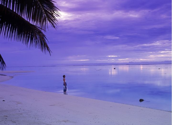 Woman alone on beach under purple dawn clouds on Rarotonga in Cook Islands