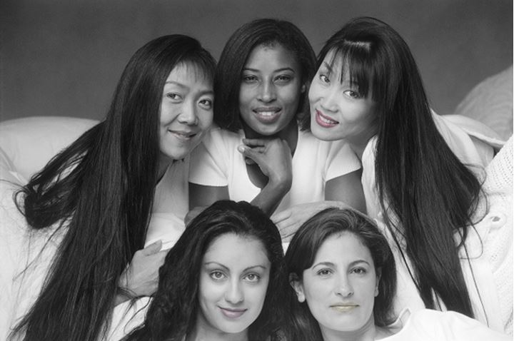 Five faces and four races in ethnic mixture of female friends