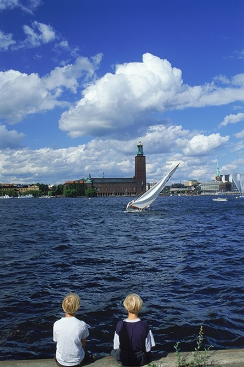 Two boys sitting on waters of Riddarfjarden with sailboat and City Hall in Stockholm