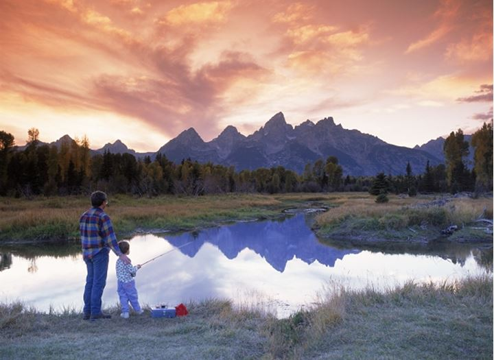 Father and son fishing in small lake at sunset below Grand Tetons near Snake River in Wyoming