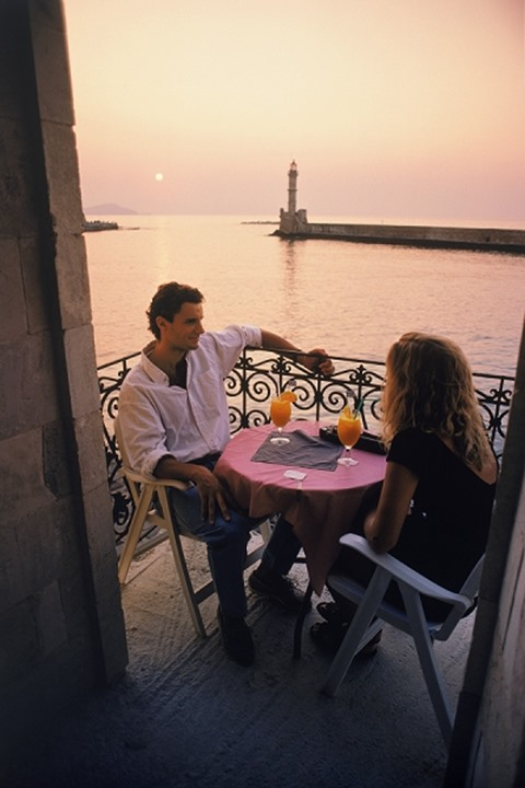 Couple on holiday in Greece having sunset drinks at Chania on Crete