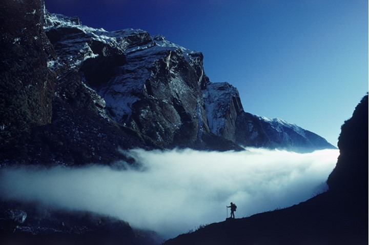 Hiker above clouds and below Macchipuchhare in Himalayas of Nepal