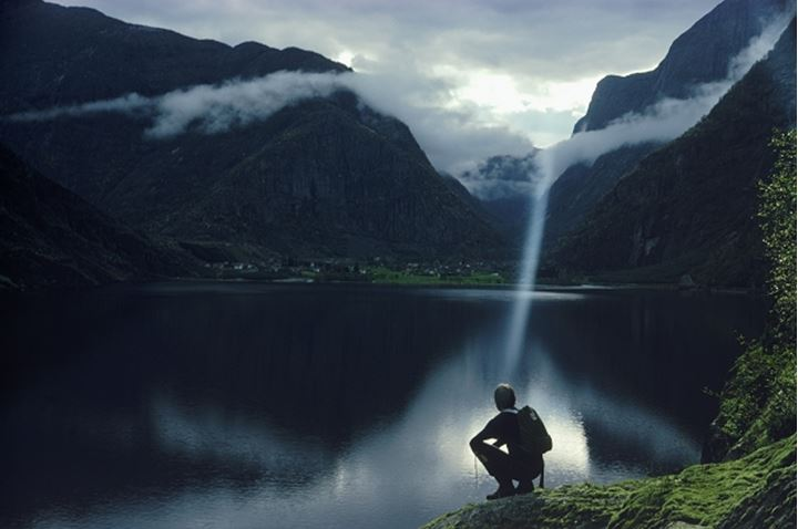 Hiker on rocky point under sun beam above Eidfjord in Norway