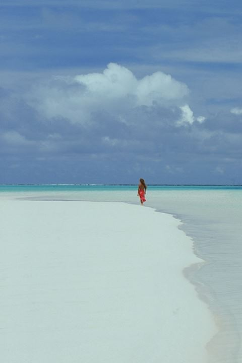 Woman in red sarong walking on sandbar in Cook Islands in South Pacific