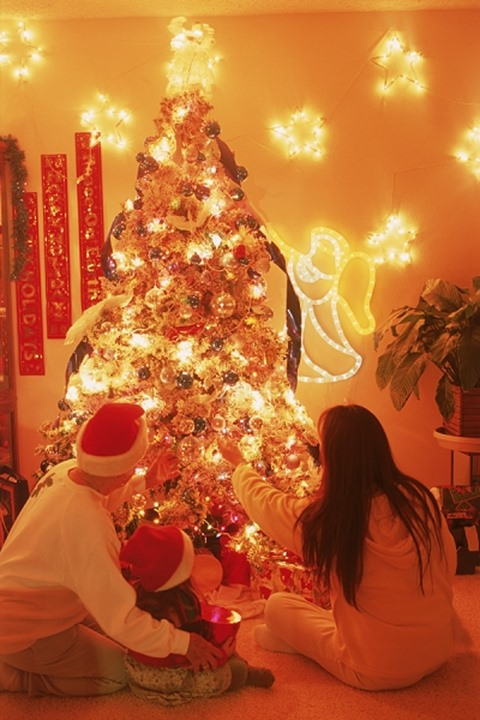 Family of three generations sitting under brightly lit Christmas tree