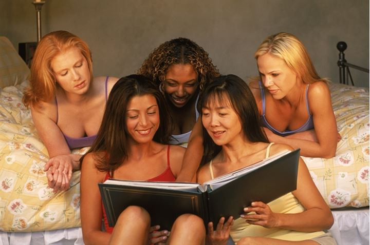 Five friends and four different races sharing photobook in bedroom