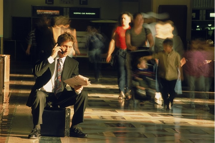 Businessman sitting on briefcase talking on cellphone and reading paper in Los Angeles Train Station