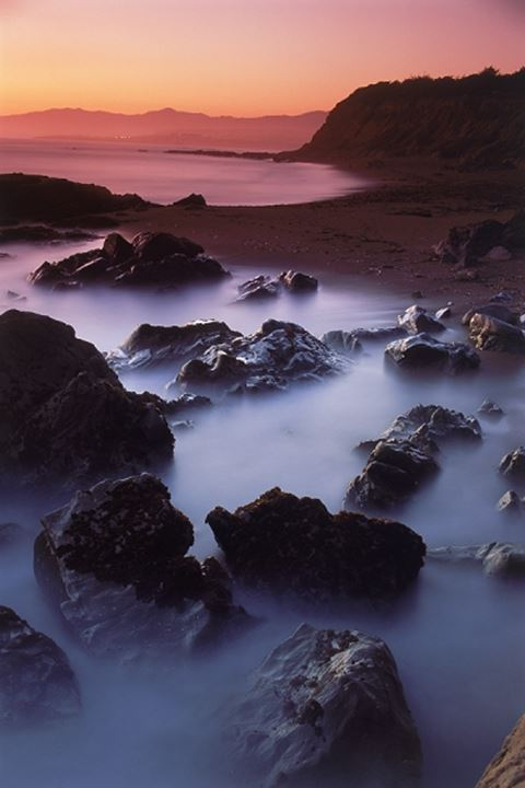 Waves painting rocky shore at sunset at Big Sur California