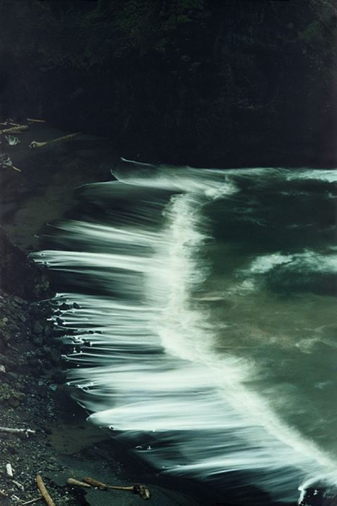 Waves sweeping across black sands and pebbles in Boardman State Park in Oregon