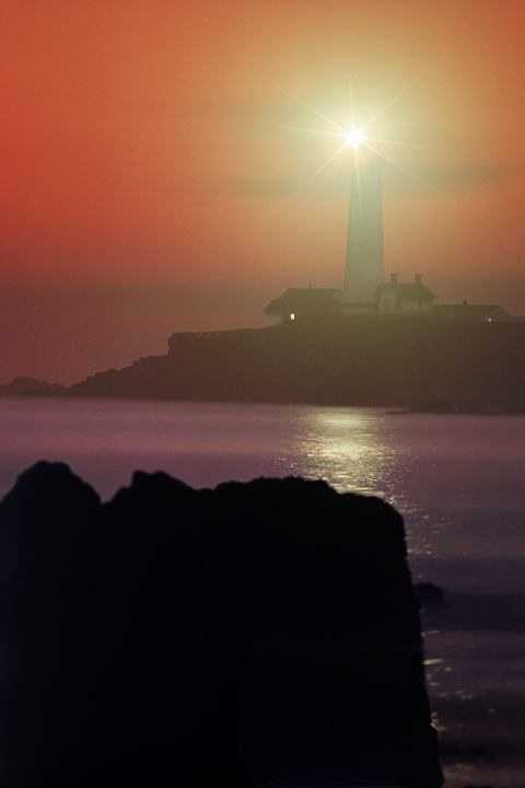 Pigeon Point Lighthouse sending beam over water to rocky shore at sunset near Santa Cruz California