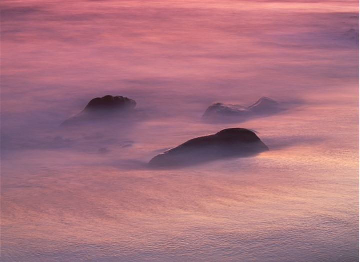Waves painting sand and rocks along Pacific shore at sunset