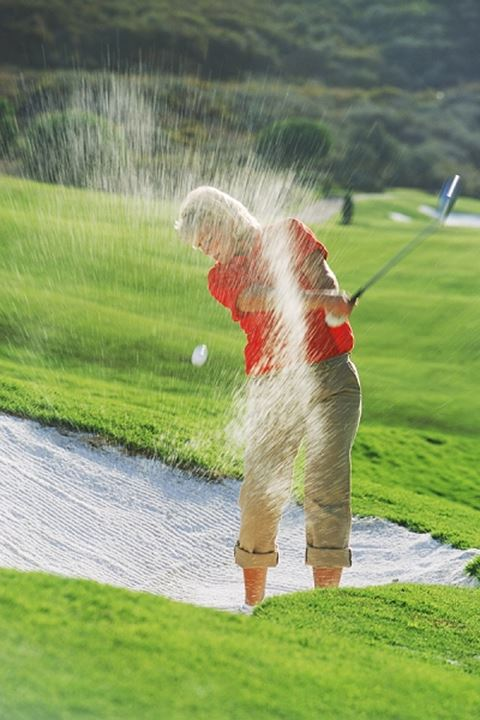 Woman golfer blasting out of sand trap