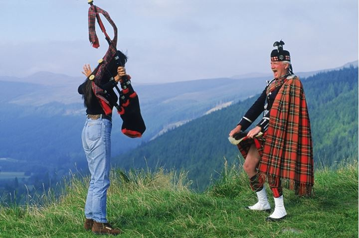 Bagpiper in Scottish Highlands letting tourist peek under his kilt