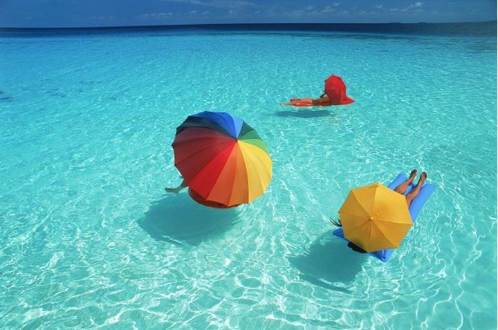 Trio of vacationers on air mattresses under colorful parasols on aqua waters
