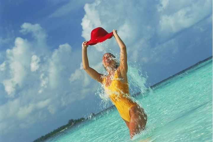 Woman pouring water from red hat over herself in tropical lagoon