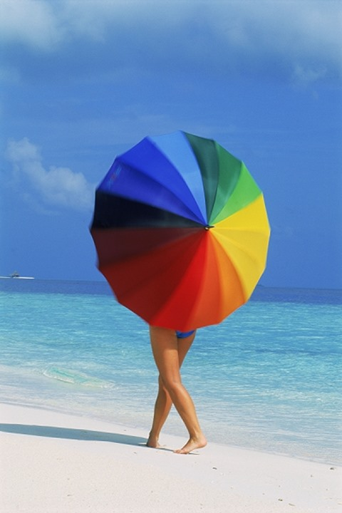 Woman walking on sandy shore spinning colorful parasol