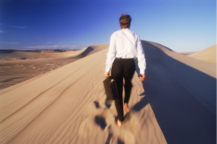 Businessman with briefcase walking on sand dune in Nevada
