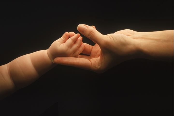 Mother and child tenderly touching hands