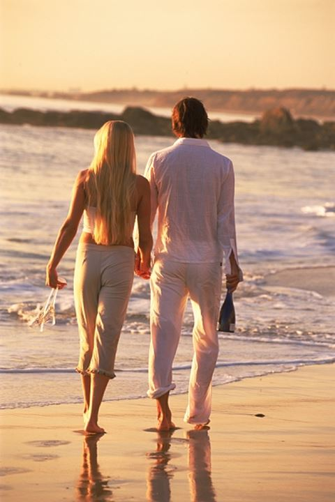 Couple with bottle of Champagne and glasses strolling shore at sunset