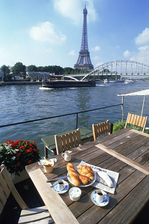 Morning paper and coffee on Seine River houseboat with Eiffel Tower