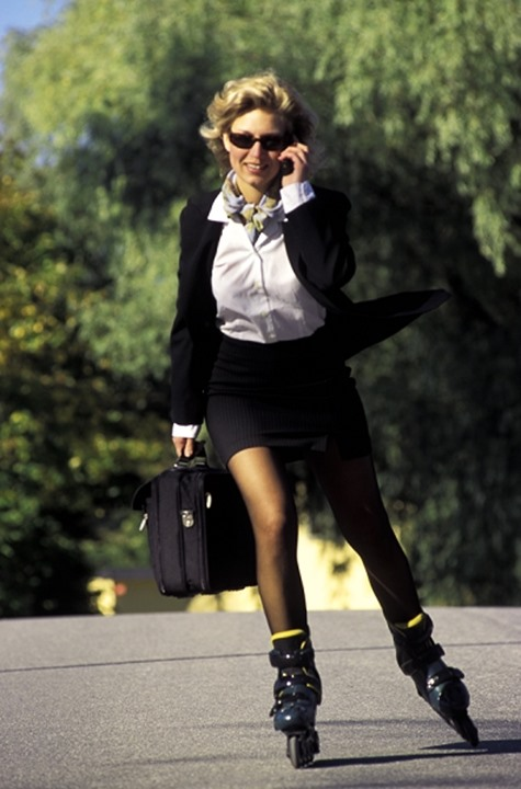 Woman with briefcase talking on cellphone while rollerblading to work