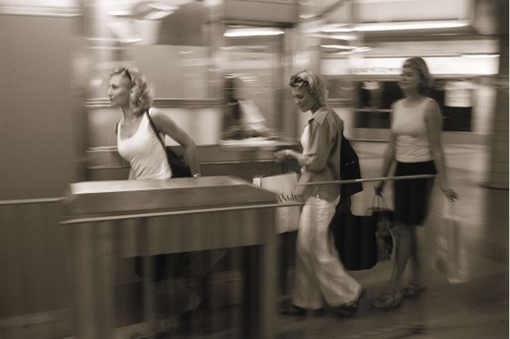 Three women with shopping bags entering underground station in Stockholm