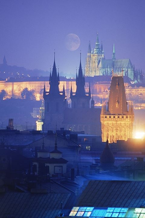 The city of 100 spires with Prague Castle and full moon at night