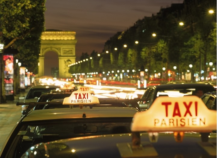 Taxicabs and traffic at night on Champs Elysees with Arc de Triomphe in Paris