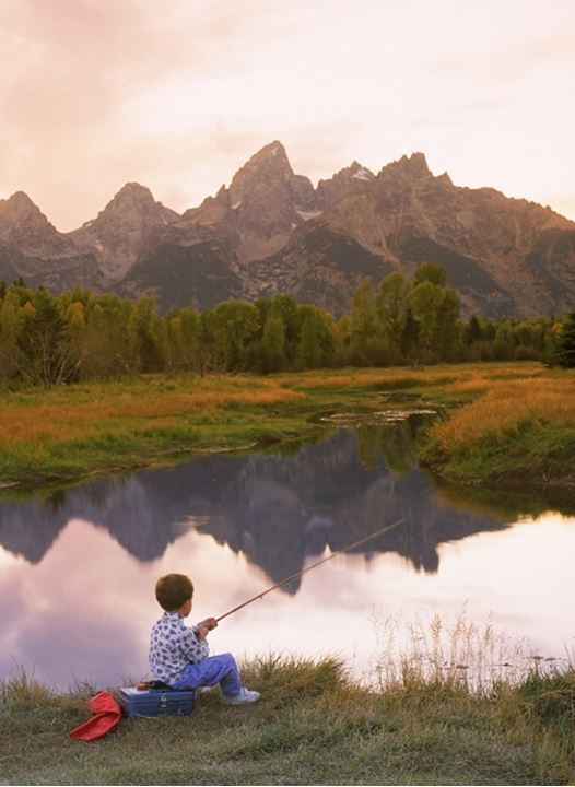 Boy fishing in pond at Ox Bow Bend of Snake River below Grand Tetons Wyoming