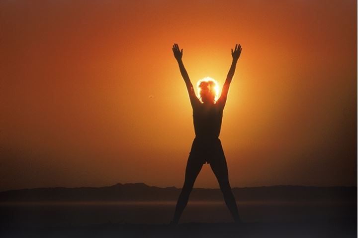 Woman silhouetted by sun in victory posture