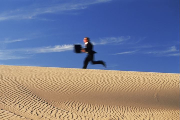 Businessman running with briefcase across sand dune