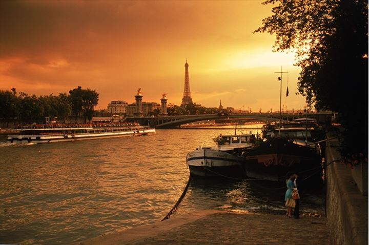 Couple near houseboats on River Seine in Paris at sunset with Eiffel Tower