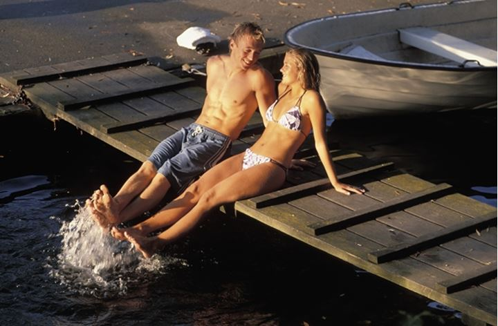 Young Swedish couple sitting on canal dock during summer in Stockholm