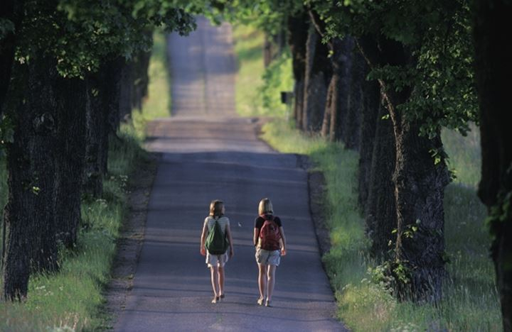 Two girls walking  on a road,