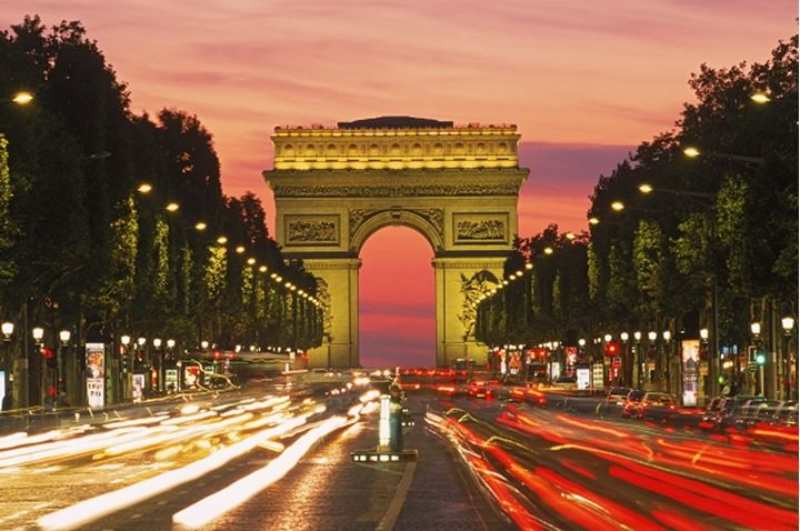 Traffic on Champs Elysees with Arc de Triomphe in Paris at dusk
